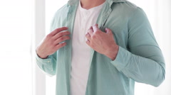 Close up of man buttoning his shirt at home Stock Footage