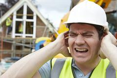 Construction suffering from noise pollution on building site Stock Photos