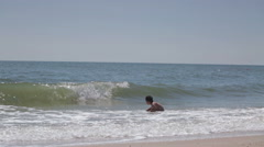 Coast sea and boy playing in waves Stock Footage