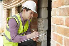 Architect checking insulation during house construction Kuvituskuvat