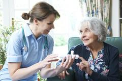 Nurse advising senior woman on medication at home Stock Photos
