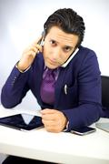 Busy businessman with two phone working at desk Stock Photos