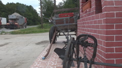 Guest rustic house near the crowded road, dog, cart and ancient agriculture plow Stock Footage