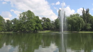 Water fountain in the middle of lake pumping at high height park reflection view Stock Footage