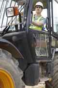 construction worker driving digger - stock photo