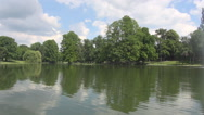 Steady water in lake inside forest, nice landscape and white clouds on blue sky Stock Footage