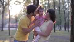 Happy family in the park, perfect father with his mother kissing daughter Stock Footage