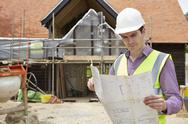 Architect on building site looking at house plans Stock Photos
