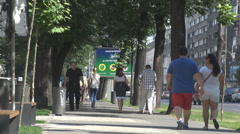 Heatwave in summer sunny day, people on pavement walking anxious commuting scene Stock Footage