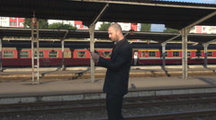 Commuting scene in station businessman with tablet walking relaxed, motion train Stock Footage