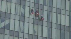 Modern climbing workers hanging in ropes cleaning business glass building danger Stock Footage