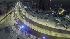 Cars ride by street at winter night in snowbound city. Stock Footage