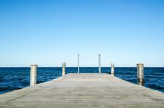 Low angle image of a wooden bath pier in blue water Stock Photos