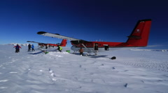 Twin otter aircraft being refueled in Antarctic wind - stock footage