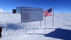 Geographic South Pole sign with Amundsen-Scott South Pole station behind Stock Footage