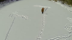 Woman in fur coat running by snow on icy rive with drawing Stock Footage