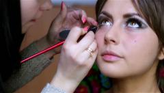 Woman in a beauty salon doing eye liner, makeup Stock Footage