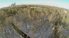 Car rides by road in snowbound forest and city on horizon - stock footage