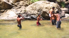 ELLA, SRI LANKA - MARCH 2014: Boys enjoying the Ravana Falls in Ella. Stock Footage