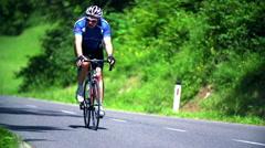 Biker on empty road pedaling Stock Footage