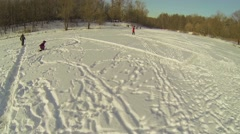 Mother with children skates by big word PLAY on snow at icy pond Stock Footage