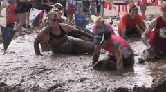 Runners running and crawling through mud pit in obstacle endurance race Stock Footage