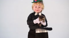 Little boy magician with green cap put kitten in hat on table Stock Footage