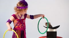 Little girl in costume magician training kitten with hoops Stock Footage