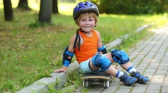 Boy in protective equipment sits on skateboard near walkway Stock Footage