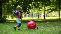 Little boy in protective equipment threw red ball for jumping Stock Footage