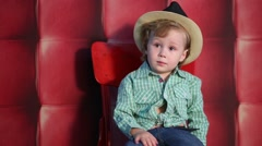 Little boy in plaid shirt, jeans and hat sitting on red chair Stock Footage