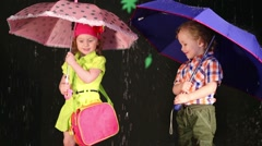 Two children with umbrellas in bright clothes and rubber boots Stock Footage