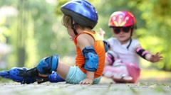 Two children in roller equipment have fun sitting on footpath Stock Footage