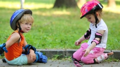 Stock Video Footage of Tired little children rest sitting on curb of walkway in park