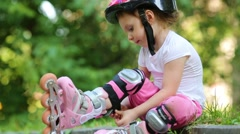Girl with rollers fastens knee-pad removes protective equipment Stock Footage