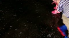Children in rubber boots run around on the puddle Stock Footage