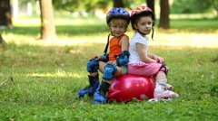 Little boy with girl sits on red ball for jumping and brakes Stock Footage