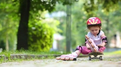 Little girl in rollers and protective equipment sitting Stock Footage