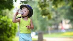 Little boy in vest drinking water from the plastic bottle Stock Footage