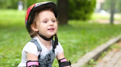 Stock Video Footage of Little girl sits on curb of walkway at park and play the ball