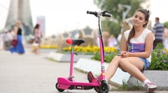 Girl with electrical scooter sits on curb of flower bed Stock Footage