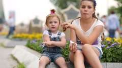 Teenager feeding girl at square with flowers, but she resists Stock Footage