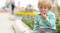 Boy in plaid shirt and jeans eating fast-food with appetite Stock Footage