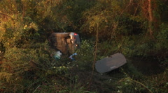 Car overturned by creek wide shot day Stock Footage