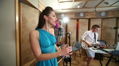 Woman sings to microphone and guy play guitar in Studio Stock Footage