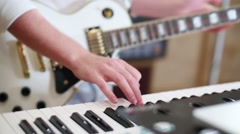 Hands of guy playing guitar and keyboard in recording studio Stock Footage
