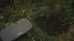 Car overturned by creek pan zoom in medium shot Stock Footage