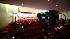 Camcorder and back of listeners on business meeting in auditorium Stock Footage