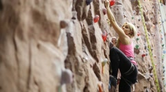 Pretty blonde woman with special equipment climbs on wall Stock Footage