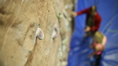 Instructor talks with girl next to climbing wall. Focus on stone Stock Footage